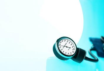 Sphygmomanometer on blue, reflective background