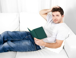 attractive man reading book or studying on couch