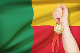 Medal in hand with flag on background - Republic of Benin