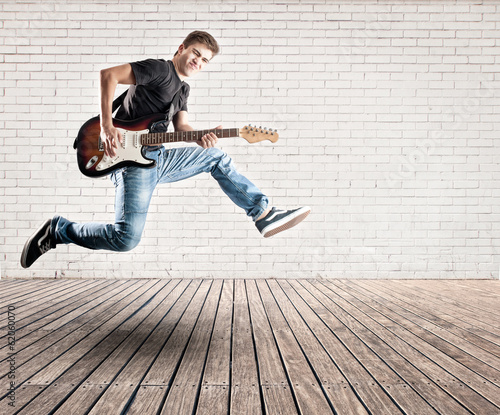 young man jumping with electric guitar
