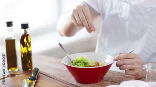 close of male hands mixing salad in a bowl