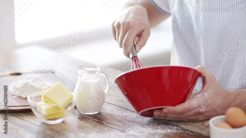 close up of male hand whisking something in a bowl