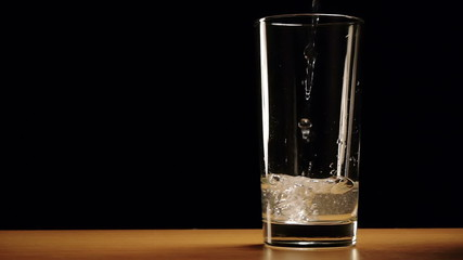 Water is slowly poured into a glass