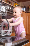 funny child 1 year old in the kitchen at dishwasher