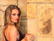 Sultry looking blonde lady next to stone wall