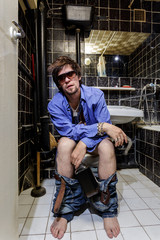Drunk Man sits in a toilet with an alcohol bottle