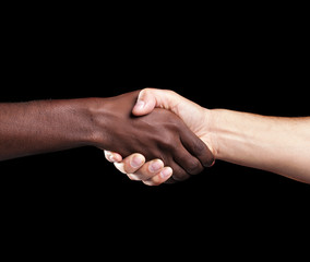 Handshake between african and a caucasian man over black backgro