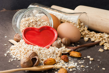 A Healthy Dry Oat meal with nut and Red heart in a wooden spoon