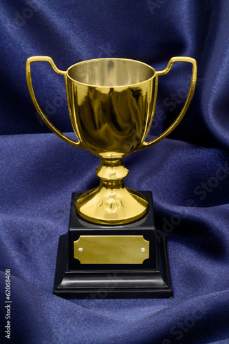 Gold Winners trophy on silk background