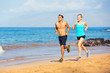 Sporty couple jogging together on the beach