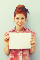 Pin-Up Girl holding blank card. Retro style imagery