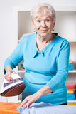 Elderly woman ironing shirt
