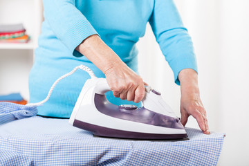Elderly lady during ironing