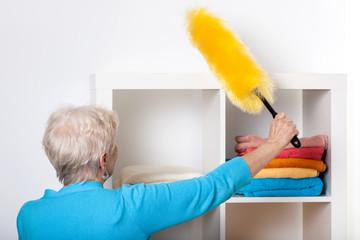 Elderly lady during dusting furniture