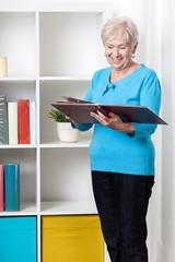 Senior lady viewing family album