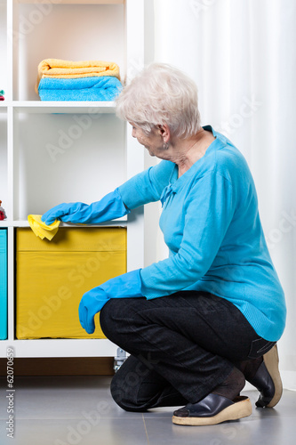 Elderly woman during dusting furniture
