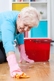 Senior woman washing floor