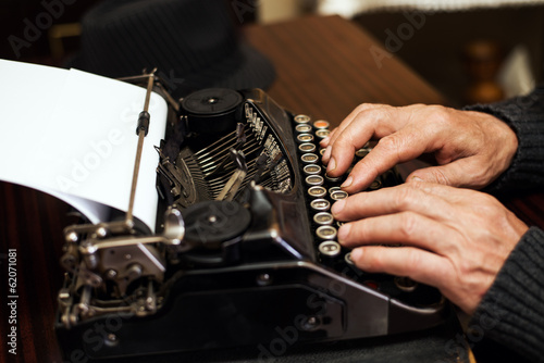 Senior man hands typing on Obsolete Typewriter.
