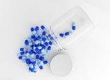 Blue capsule pills spilled on white background