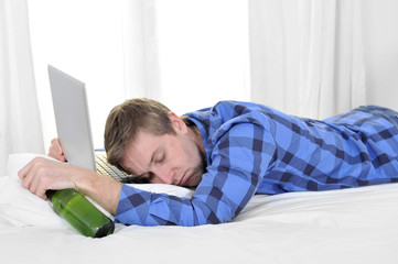 student overworked asleep on computer holding beer bottle