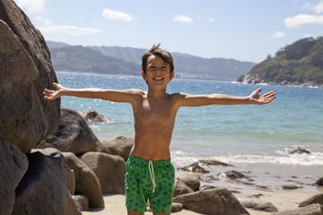 Niño con los brazos abiertos y alegre en la playa
