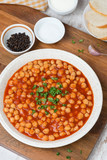 chickpeas in tomato sauce with fresh herbs, top view