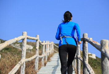 young sporty woman running up on stairs to the  mountain peak