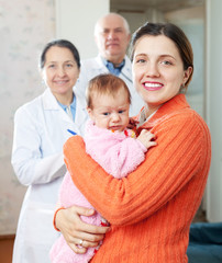 woman holding baby with doctors