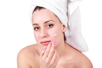 Woman applying cream on acne or skin blemishes