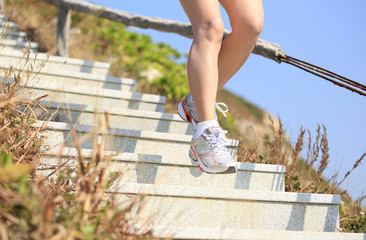 sporty woman legs running on mountain stairs