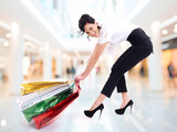 Happy attractive woman drags shopping bags.