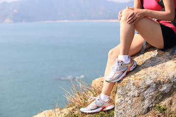 hiking woman sit on seaside mountain rock