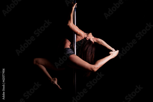 Poster Fitness Sexy pole dancer in dark setting