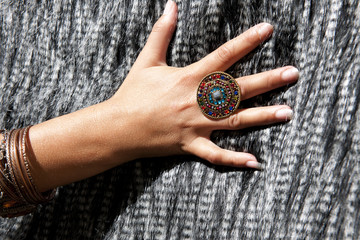 Woman's hand with big ring and bracelets