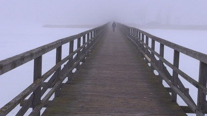 dark morning fog on wooden bridge and one schoolboy