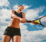 Female tennis player serving. Shot from a low angle against blue