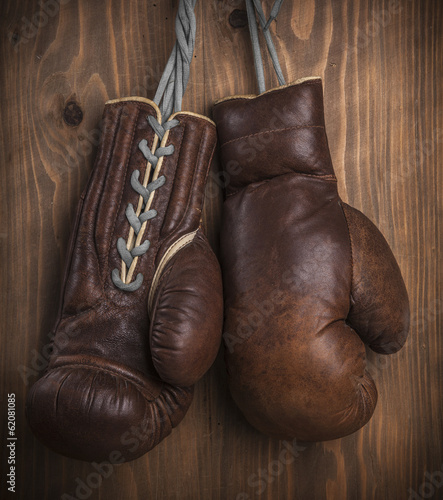 Old boxing gloves with a lace over old wooden wall