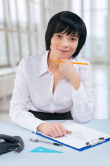 asian businesswoman sitting at table and looking at camera