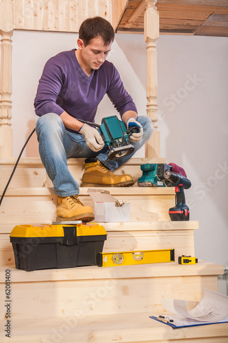 a young carpenter sitting on step of wooden ladder holding and l