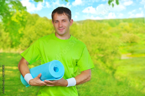 a young sportsman standing on nature and holding yoga mat