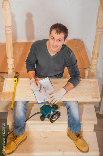 a young handsome man wearing working clothes sitting on ladder a