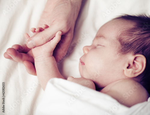 canvas print picture Newborn baby and his father's hand - care and safety concept