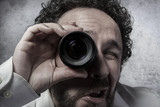 Businessman looking through a lens, man in white shirt with funn