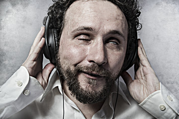 listening and enjoying music with headphones, man in white shirt