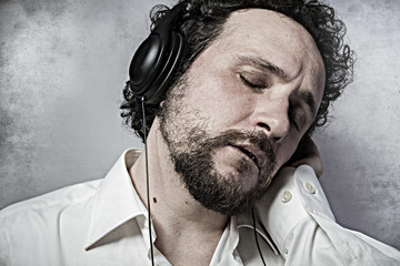 Joy, listening and enjoying music with headphones, man in white
