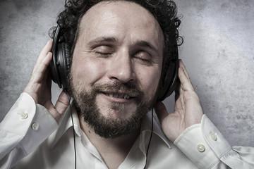 listening and enjoying music with headphones, man in white shirt