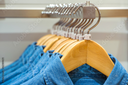 Jeans shirts on the hangers in the clothing store