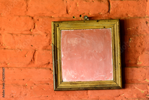 Square mirror on a brick wall