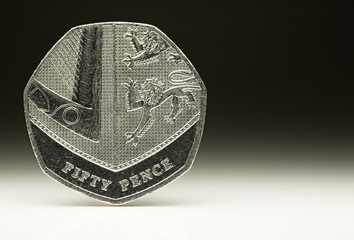 New UK Fifty Pence Coin balancing on white, money concept