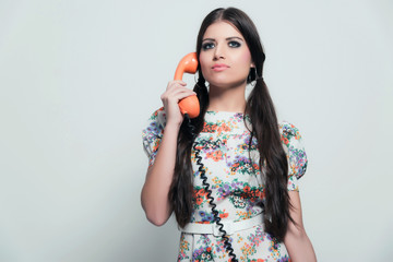 Retro 70s fashion. Pretty brunette girl with long hair. Calling